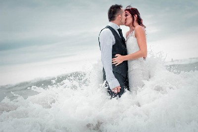 trash the dress in the sea on the rocks with waves in italy