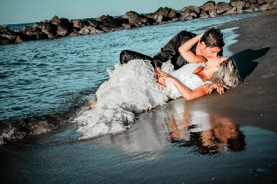 trash the dress at the sea river on the sunset close to rocks in italy